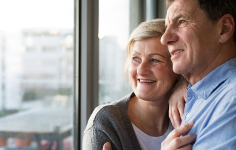 senior couple in living room standing at the window hugging